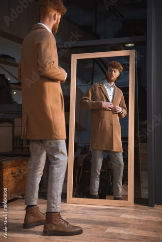 Cuadros en Lienzo stylish young man wearing overcoat and looking at mirror in boutique