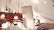 young woman lies on a bed with a laptop on a garland background, video chat