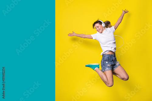 Fotografie, Obraz  young woman listening music and jumping on yellow background