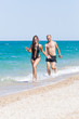Barefoot young woman and man swimwear running along seashore