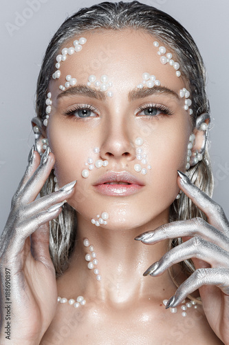 Fotografia  Beautiful woman portrait with pearl beads on face, silver hair and wet skin and sinver hands