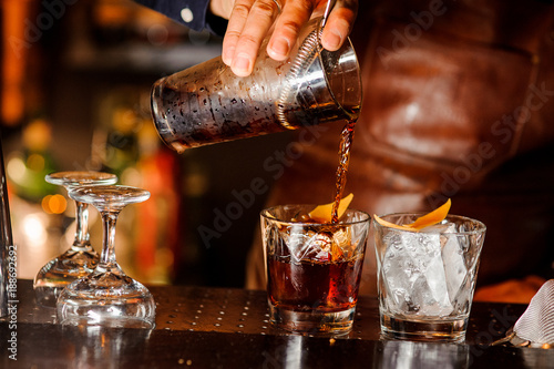 Barman pouring alcoholic drink into the glasses