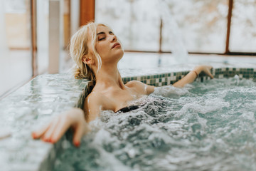 Young woman relaxing in the whirlpool bathtub