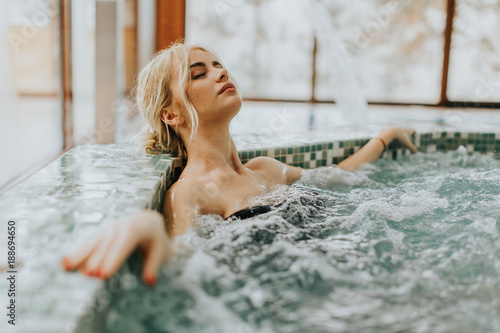 obraz PCV Young woman relaxing in the whirlpool bathtub