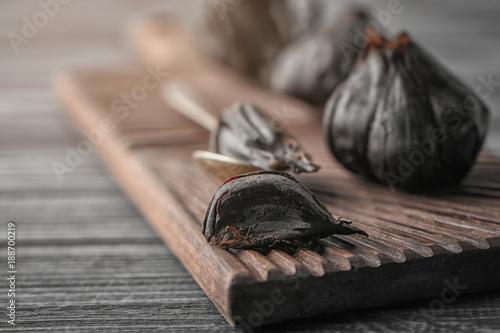 Black garlic (Allium sativum) on wooden board