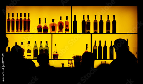 Fotografía  silhouette of people against of a bar
