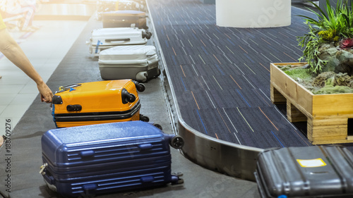 suit case on luggage conveyor belt at baggage claim in airport terminal Canvas Print