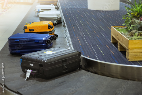 suit case on luggage conveyor belt at baggage claim in airport terminal Wallpaper Mural