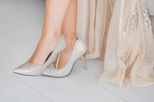 Closeup View Of Female Legs In Silver Shiny High Heels. Beautiful Young Woman In Long Gorgeous Dress Indoors. Horizontal Color Photography.