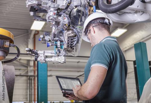 Foto  Ingenieur prüft Roboter bei Inbetriebnahme einer Produktionsanlage für Automobil