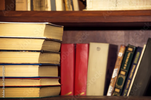 A Stack Of Old Books On The Background Bookshelves