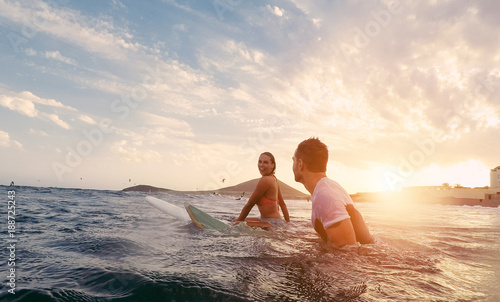 Foto  Fit couple surfing at sunset