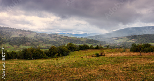 Panoramic view of the mountain scene, rainy misty landscape. Seasonal changes from summer to autumn, nature background