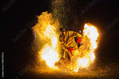 A stunning fire show against a dark night. A man in a chemical protection suit and a gas mask plays with fire