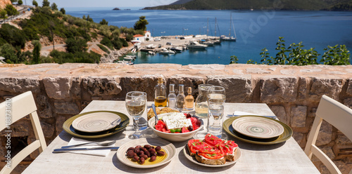 A table served for two with snacks and drinks on the summer terrace of the hotel room by the seascape.