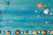 Marine motifs. Various seashells on a blue wooden background with copy space.