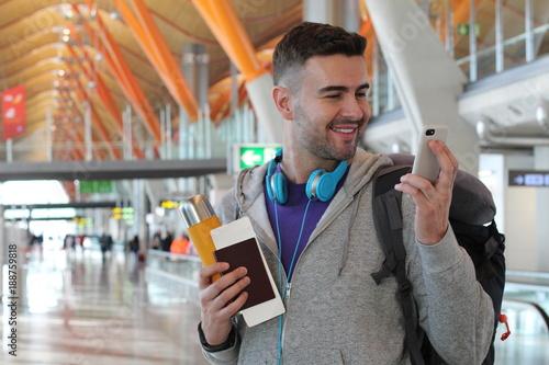 Joyful traveler using smartphone in the airport