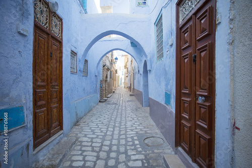 Staande foto Tunesië old wooden doors and blue walls on the street in old town in Tunisia