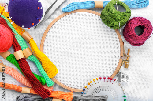 Fototapeta Colorful threads and embroidery hoop with fabric, top view