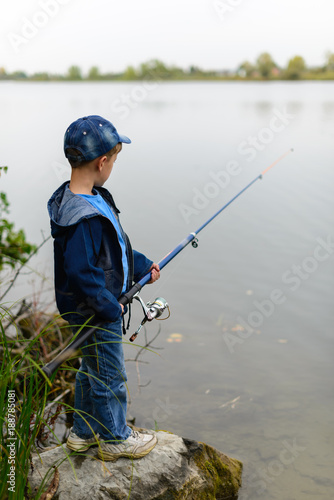 Fotobehang Vissen A fisherman boy on the river bank with a fishing rod in his hands. He wants to catch a big fish..