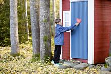 Side View Of Boy Hanging Heart On Door