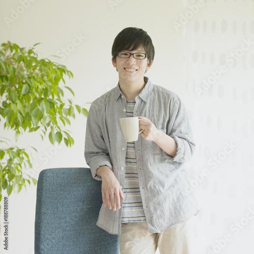 コーヒーカップを持ち微笑む男性