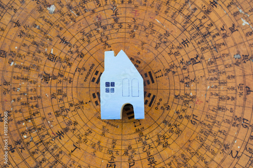 Blue wooden miniature house on blurred ancient feng shui compass background Poster