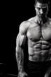 Bodybuilder posing in front of black background
