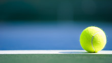One New Tennis Ball On White Line In Blue And Green Hard Court With Light From Right, Shadow And Copy Space On Left