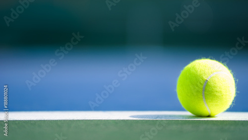 Fotografie, Obraz one new tennis ball on white line in blue and green hard court with light from r