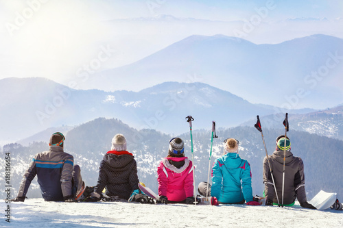 Skiers looking mountain hilles while sitting on snow, back view