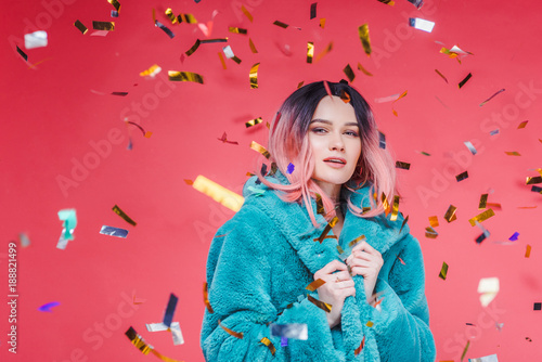 Obraz stylish glamour girl with pink hair posing in blue fur coat, isolated on pink with confetti - fototapety do salonu