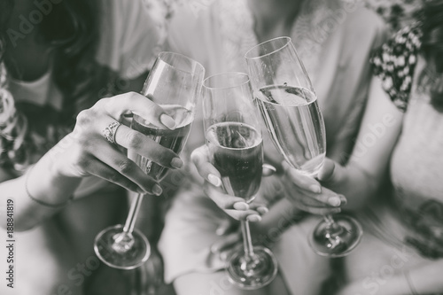 Closeup view of three female young hands holding wineglasses with champagne. Future bride with her girlfriends celebrating. Black and white photography.