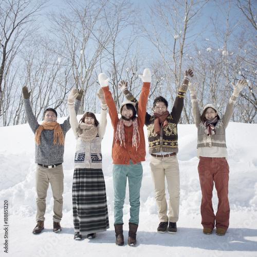 雪道で両手を挙げる若者たち