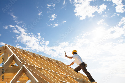 Fototapeta roofer carpenter working on roof structure on building site obraz
