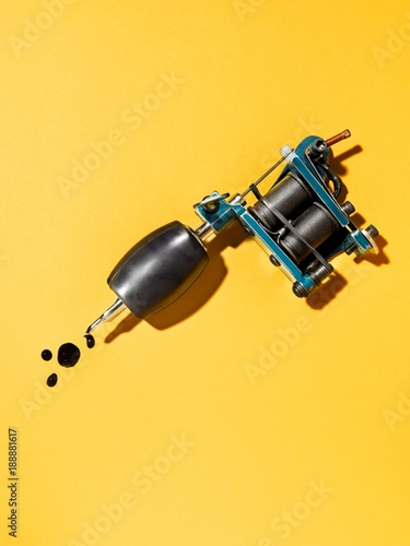 Tattoo gun against yellow background