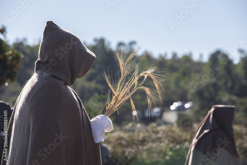 Fotografía  Hooded entourage members with wheat bundle offering