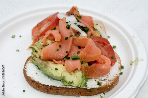 Fotografie, Obraz  Avocado toast with smoked salmon on white plate and table outdoors