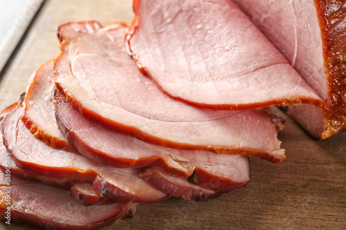 Delicious sliced honey baked ham on wooden board, closeup