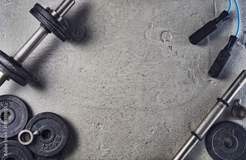 Poster Fitness Fitness or bodybuilding concept background. Product photograph of old iron dumbbells on grey, conrete floor in the gym. Photograph taken from above, top view with lots of copy space