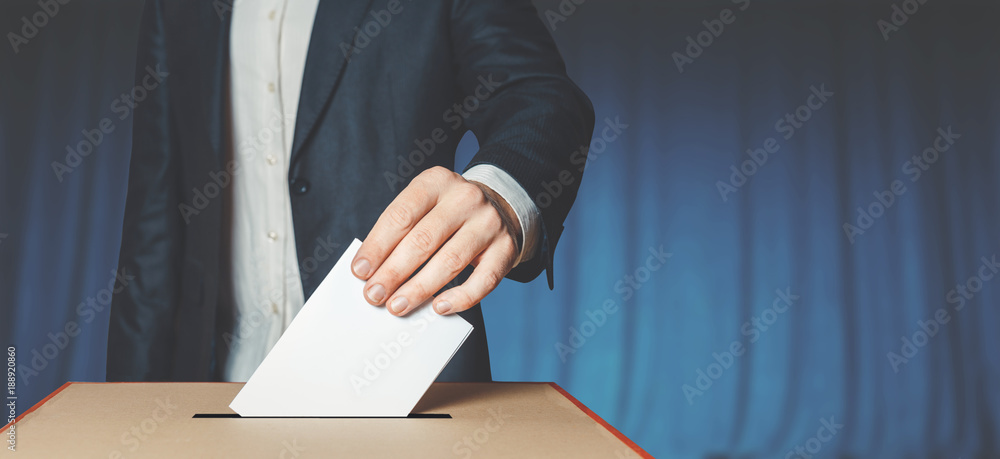 Fototapety, obrazy: Man Voter Putting Ballot Into Voting box. Democracy Freedom Concept Near Blue Wall