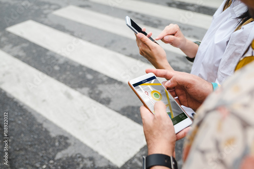 Traveler use map on mobile phone app to search for route location of place with gps on street when travel in city,Technology in lifestyle .