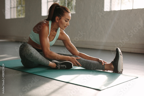 Fit woman doing stretching workout at gym Fototapeta