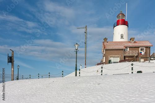 Zdjęcie XXL Holenderska zima ze śniegiem i widokiem na latarnię wioski rybackiej Urk