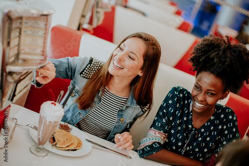 Foto  Gemischtrassige Freundinnen, die Schnellimbiß an einem Tisch im Restaurant essen