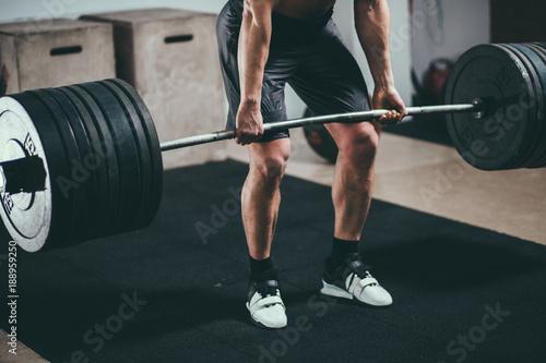 Fényképezés  Muscular fitness man doing deadlift barbell in modern fitness center