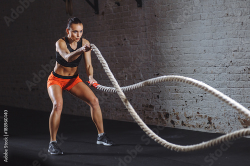 Obraz Woman training with battle rope in cross fit gym - fototapety do salonu