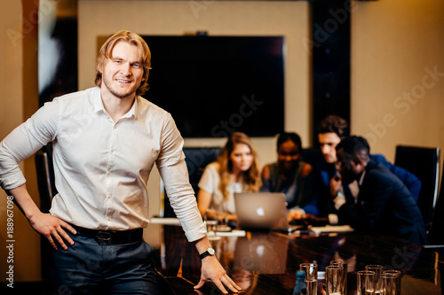 Fototapety, obrazy: Portrait of Young businessman looking at camera with blurred workers on background