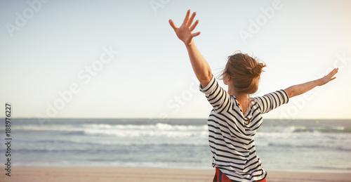 Obraz happy woman enjoying freedom with open hands on sea - fototapety do salonu