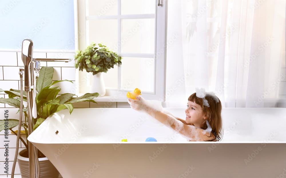 Fototapeta  Happy little baby girl sitting in bath tub  in the bathroom
